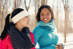 Paires multi-ethniques d'amis féminins faisant une pause de pulser dans la neige en hiver Photo stock