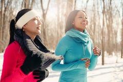 Paires multi-ethniques d'amis féminins faisant une pause de pulser dans la neige en hiver Photographie stock libre de droits
