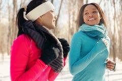 Paires multi-ethniques d'amis féminins faisant une pause de pulser dans la neige en hiver Photos stock