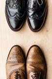 Paires noires et brunes de chaussures en cuir sur le plancher en bois images libres de droits