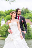 Paires nuptiales en parc, marié tenant la jeune mariée Photos libres de droits