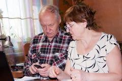 Paires pluses âgé à la table avec un carnet Photographie stock