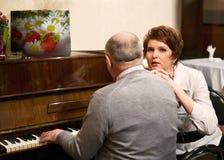 Paires pluses âgé en café au piano Image libre de droits