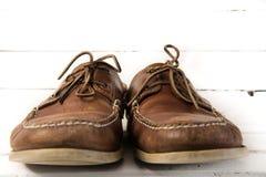 Paires portées de chaussures en cuir occasionnelles brunes devant le fond en bois blanc Image stock