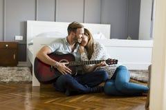 Paires romantiques jouant la guitare sur le plancher Image stock