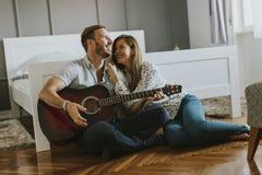 Paires romantiques jouant la guitare sur le plancher Photographie stock