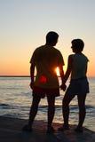 Paires romantiques regardant l'un l'autre le coucher du soleil Images libres de droits