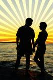 Paires romantiques regardant l'un l'autre le coucher du soleil Photos stock