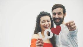 Paires tendres aimantes sur le fond blanc Gens sérieux Une femme douce avec son mari tient un mot en bois pour l'amour dedans banque de vidéos