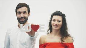 Paires tendres aimantes sur le fond blanc Gens sérieux Une femme douce avec son mari tient un mot en bois pour l'amour dedans clips vidéos