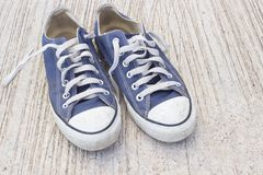 Pairs of canvas blue shoes on the wood background , dirty blue s Stock Photos