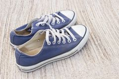 Pairs of canvas  blue shoes on the wood background , dirty blue s Stock Photo