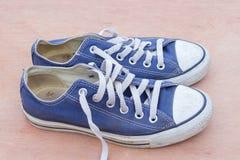 Pairs des chaussures bleues de toile sur le fond en bois, bleu sale s Images libres de droits