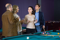 Pairs of different ages, talking with glasses of wine in a billiard hall. Two pairs of different ages, talking with glasses of wine in a billiard hall stock photography