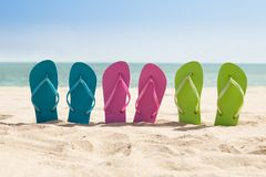 Pairs of flip-flops on beach Royalty Free Stock Image