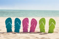 Pairs of flip-flops on beach Royalty Free Stock Images