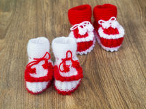 Pairs of handmade white and red knitted slippers Stock Photos