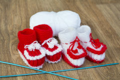 Pairs of handmade white and red knitted slippers and yarn ball Royalty Free Stock Photos