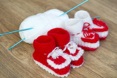 Pairs of handmade white and red knitted slippers and yarn ball Royalty Free Stock Images