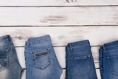 Pairs of jeans on showcase. Women`s and men`s clothing. Denim lovers, season sale concept Stock Photos