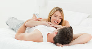 Pairs lying down together in their bed at home Stock Photo
