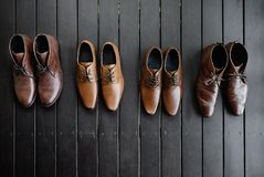 4 pairs of men's brown shoes on the black wooden floor royalty free stock images