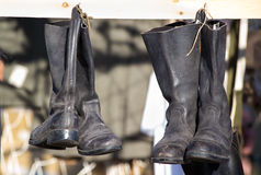 Pairs of old boots hanging in a military camp Royalty Free Stock Image