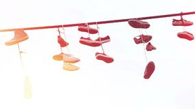 Pairs of shoes dangling hanging on power lines to promote street gang zone. Stock footage stock video