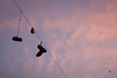 Pairs of shoes flung. Over electric wire by shoelaces Stock Images