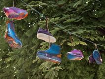 Pairs of shoes laced with laces hanging on the cord stock photo