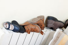 Pairs of shoes on   radiator Royalty Free Stock Images