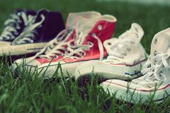 Pairs of sneakers in green grass. On the garden Stock Photography