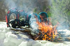 2 pairs of snow shows are planted in the snow on the side of a small camp fire royalty free stock photography
