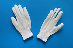 Pairs of white color working hand gloves. Flat lay of white color gardening or working hand gloves on blue background royalty free stock images