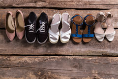 Pairs of woman's stylish footwear. Shoes on old wooden shelf. Shoe row at vintage store. Retro boutique footwear sale royalty free stock photography