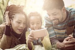 Pais afro-americanos com sua filha no parque usando mobil foto de stock royalty free