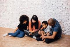Pais afro-americanos que leem uma história da fábula do conto de fadas para crianças em casa Família feliz que senta-se no assoal imagens de stock