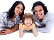 Pais alegres com seu filho que encontra-se no assoalho Imagem de Stock