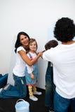 Pais alegres com suas crianças que pintam um quarto Fotos de Stock Royalty Free