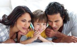 Pais alegres que escutam a música com seu filho imagens de stock