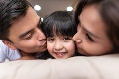 Pais asiáticos que beijam sua pouca filha em ambos os mordentes fotos de stock
