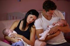 Pais cansados que afagam filhas gêmeas do bebê no berçário Fotografia de Stock