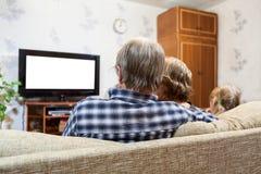 Pais caucasianos e filha que sentam-se no sofá e na tevê de observação, tela branca isolada Imagens de Stock Royalty Free