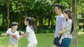 Pais chineses que sorriem & que olham as crianças que jogam no parque no verão Fotos de Stock