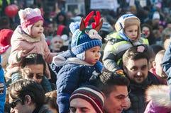 Pais com as crianças em ombros Imagens de Stock