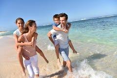 Pais com as crianças no seu passeio traseiro na praia foto de stock