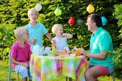 Pais com as crianças que têm o almoço fora imagem de stock
