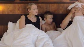 Pais com bebê e filho da pessoa idosa na cama filme