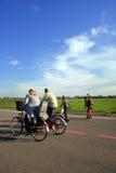 Pais com bicicletas e crianças com rollerblades Foto de Stock Royalty Free