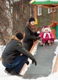 Pais com a criança que joga na corrediça Fotografia de Stock